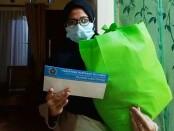 Salah satu wartawan anggota PWI Jateng di Semarang yang terpapar Covid-19, saat menerima bantuan dari program Jogo Wartawan - foto: Sujono/Koranjuri.com