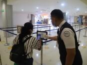 Calon penumpang di Bandara Ngurah Rai Bali melakukan barcode scanning aplikasi PeduliLindungi - foto: Istimewa