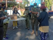 Anggota Satpol PP Provinsi Bali bersama relawan membagi-bagikan 200 bungkus lauk pauk di Parkir Timur Lapangan Renon Denpasar, Jumat (23/7/2021) sore - foto: Istimewa
