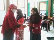 Kepala SMK Batik Purworejo,  Yati Dwi Puspita Adi, S.Pd, saat menyerahkan bantuan kepada siswa yatim, Kamis (19/08/2021) - foto: Sujono/Koranjuri.com