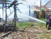 Petugas Damkar mencoba menjinakkan api akibat kebakaran bedeng bedeng pekerja proyek RSUD Buleleng