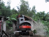 Alat berat sedang merobohkan bangunan liar di komplek lokalisasi Gunung Tugel, Kutoarjo - foto: Sujono/Koranjuri.com