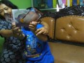 Korban FR berusia 5 tahun bersama ibunya menunjukkan foto-foto penganiayaan yang menimpa dirinya - foto: Djoko Judiantoro/Koranjuri.com