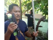 Seorang anggota polisi menunjukkan senjata tajam yang disita dari anggota ormas - foto: ist