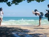 Wisatawan di Pantai Kuta Bali memanfaatkan momen gelombang tinggi untuk berfoto - foto: Wahyu Siswadi/Koranjuri.com