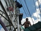 Sejumlah petugas berusaha membujuk Agustinus yang nekad memanjat tiang baliho untuk menyampaikan masalahnya - foto: Istimewa
