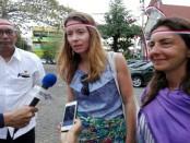 Sophia (kiri) turis asing asal Portugal dan Mariana (kanan) asal Brazil tampak melilitkan pita merah putih di kepalanya - foto: Koranjuri.com