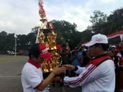Wakil Gubernur Bali I Ketut Sudikerta menyerahkan piala juara umum I kepada pemenang Kabupaten Badung di Porprov Bali XIII di Lapangan Astina Gianyar - foto: Koranjuri.com