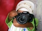 Rosidah menunjukkan teknis memegang kamera dengan DSLR miliknya - foto: Sujono/Koranjuri.com