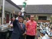 Kepala SMK PGRI 3 Denpasar, I Nengah Madiadnyana mengangkat piala untuk siswa yang meraih juara umum empat kali berturut-turut di event tingkat provinsi Bali - foto: Koranjuri.com
