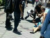 Korban Kampek (40) terkapar setelah dianiaya oleh pelaku Kadek Jaya (24). Sementara, warga membekuk pelaku Kadek Jaya usai melakukan penganiayaan - foto: Istimewa