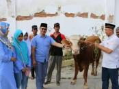 Kapolres Kebumen, AKBP Arief Bahtiar saat menyerahkan hewan qurban secara simbolis kepada ketua panitia penyembelihan hewan qurban, Kompol Yuliono - foto: Sujono/Koranjuri.com