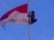 Anggota Kodim 1603/Sikka Sertu Kristianus Sina memanjat tiang bendera ketika ujung tali bendera tersangkut saat upacara penurunan bendera memperingati HUT Kemerdekaan Ke-73 di  Kelurahan Belu, Kecamatan Alok Timur, Kabupaten Sikka, NTT, pada jumat (17/8/2018) - foto: Istimewa