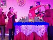 Bupati I Nyoman Giriprasta memberikan potongan tumpeng pertama kepada Dirut PDAM Badung I Ketut Golak - foto: Koranjuri.com