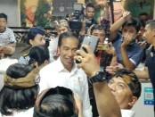 Presiden Joko Widodo melayani ajakan selfi masyarakat saat meresmikan pasar Badung di Denpasar, Bali pada Jumat, 22 Maret 2019 - foto: Koranjuri.com