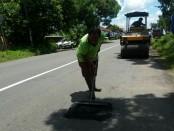 Petugas tengah melakukan penambalan pada salah satu ruas jalan, sebagai akibat dari dampak banjir yang terjadi pada pertengahan Maret lalu - foto: Sujono/Koranjuri.com