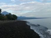 Pasir hitam di sepanjang pantai Amed, Karangasem Bali berlatarbelakang Gunung Agung - foto: Koranjuri.com