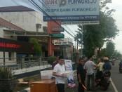 Dirut Bank Purworejo, Wahyu Argono Irawanto, SE, MM, saat membagikan takjil pada pengguna jalan yang kebetulan melintas di depan kantor Bank Purworejo - foto: Sujono/Koranjuri.com