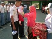 Penyematan tanda peserta kepada perwakilan siswa oleh Kepala Sekolah, Samsiyah, S.Pd, menandai dimulainya kegiatan MPLS (Masa Pengenalan Lingkungan Sekolah) di SMKN 7 Purworejo - foto: Sujono/Koranjuri.com