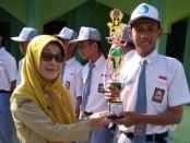 Kepala SMK N 7 Purworejo, Samsiyah, SPd, saat menerima piala dari siswa peraih juara, untuk diserahkan ke sekolah - foto: Sujono/Koranjuri.com