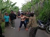 Warga petani yang menggarap lahannya di Dusun Selasih, Desa Puhu, Kecamatan Payangan, Kabupaten Gianyar, Bali berusaha menghalau alat berat yang didatangkan di lokasi, Sabtu, 23 November 2019 - foto: Istimewa