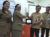 Deputi Direksi Wilayah Bali NTT, NTB BPJS Kesehatan dr. I Made Puja Yasa menyerahkan cenderamata kepada Sekdis Koperasi Provinsi Bali Dra. Ni Nyoman Widarti, M.Si - foto: Koranjuri.com