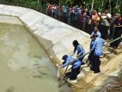 Wabup Purworejo Yuli Hastuti, saat menabur ribuan benih ikan di embung Desa Sidomulyo, Purworejo, Jum'at (17/1) - foto: Sujono/Koranjuri.com