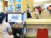 Petugas melakukan deteksi suhu tubuh terhadap wisatawan melalui body thermo scanner di terminal kedatangan internasional Bandara Ngurah Rai, Bali - foto: Istimewa