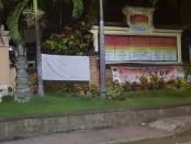 Salah satu spanduk penolakan proyek Taman yang terpasang di depan Kantor Desa Lebih Gianyar, Minggu (29/3/2020) - foto: Catur/Koranjuri.com