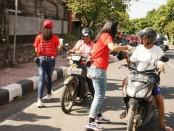 KONI Gianyar ketika memberikan selebaran kertas berisikan pencegahan penyebaran Covid-19 kepada pengendara motor yang lewat di Jalanan Kota Gianyar, Jumat (3/4/2020) - foto: Catur/Koranjuri.com