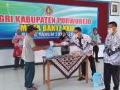 Ketua PGRI Kabupaten Purworejo, Irianto Gunawan, saat menyerahkan secara simbolis bantuan paket sembako kepada tukang becak, Kamis (9/4), di aula PGRI - foto: Sujono/Koranjuri.com