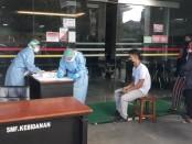 Petugas medis ber APD lengkap melakukan screening test terhadap setiap pengunjung maupun petugas yang hendak memasuki area Rumah Sakit Sanjiwani Gianyar, Minggu (12/4/2020) pagi - foto: Catur/Koranjuri.com
