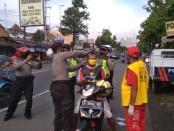 Polsek Kutoarjo, Purworejo, bekerja sama dengan Klenteng Hok Tik Bio, membagi ribuan masker kepada masyarakat Kutoarjo, Kamis (16/4/2020) - foto: Sujono/Koranjuri.com