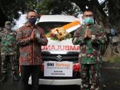 Pimpinan wilayah BNI Bali Nusra I Made Sukajaya menyerahkan satu unit mobil ambulans yang diterima oleh Pangdam IX/Udayana Mayjen TNI Benny Susianto, Rabu, 20 Mei 2020 - foto: Istimewa