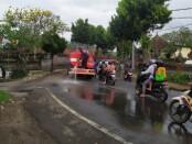 Petugas dari Pemadam Kebakaran (Damkar) Kabupaten Gianyar saat melakukan penyemprotan untuk membersihkan tumpahan solar di Jalan Raya Wanayu, Bedulu, Blahbatuh Gianyar, Sabtu (1/8/2020) kemarin - foto: Catur/Koranjuri.com