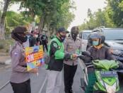 Keterangna foto : Aksi simpatik mitra gojek membagikan masker dan mengedukasi pentingnya menjaga kesehatan./ Foto: istimewa