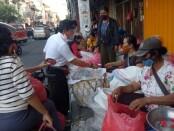 Sebelum menebar 5.000 ekor benih ikan Nila di Tukad Badung, pasangan nomor urut 2 ini membagikan masker dan baju kaos kepada para pedagang dan pembeli di seputaran pelataran parkir pasar Badung dan pasar Kumbasari - foto: Istimewa