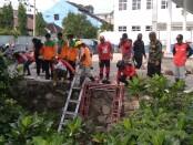 Puluhan relawan dari berbagai komunitas membersihkan sungai di jalan bhayangkara solo - foto: Koranjuri.com