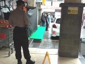 Petugas kepolisian dan keamanan berjaga di sekitar bilik ATM sebuah super market di Jalan Buluh Indah, Denpasar, Senin, 25 Januari 2021 - foto: Koranjuri.com