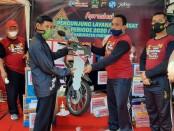Kepala UPPD Kabupaten Purworejo, Roedito Eka Suwarno, saat memberikan hadiah doorprize berupa sepeda motor kepada Syamsudin, warga Cokroyasan, Grabag - foto: Sujono/Koranjuri.com