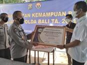 Penyerahan piagam penghargaan oleh Ketua SMSI Provinsi Bali kepada Kabid Humas Polda Bali Kombes Pol Samsi pada pelatihan 'Peningkatan Kemampuan PID Jajaran Polda Bali TA. 2021' - foto: Koranjuri.com
