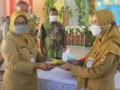 Pemotongan tumpeng oleh Kepala SMAN 2 Purworejo Dra Fitarini, M.Si, dan diberikan kepada Pungky Ayu Yulitasari, S.Pd, guru mapel PPKn, dan ASN termuda, Senin (05/07/2021), menandai puncak peringatan HUT SMAN 2 Purworejo yang ke 41 - foto: Sujono/Koranjuri.com