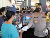 Kapolres Tabanan AKBP Ranefli Dian Candra S.I.K, M.H., membagikan masker kepada buruh jinjing di pasar tradisional Kediri, Tabanan, Senin, 16 Agustus 2021 - foto: Istimewa