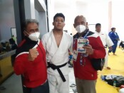 Gede Ganding Kalbu Soetama diapit kedua pelatihnya usai meraih emas di PON XX Papua - foto: Yan Daulaka/Koranjuri.com